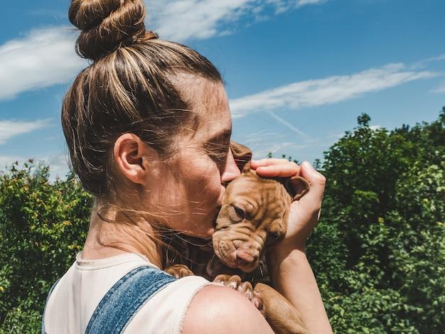 Donna che tiene grazioso cucciolo di cioccolato
