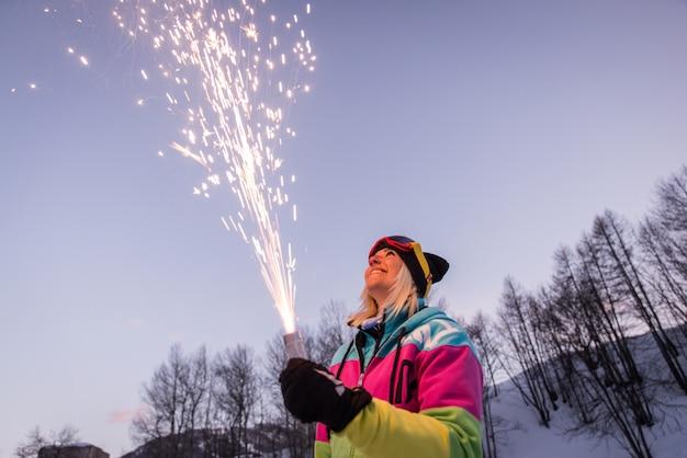 Donna che tiene i fuochi d'artificio di una stella filante