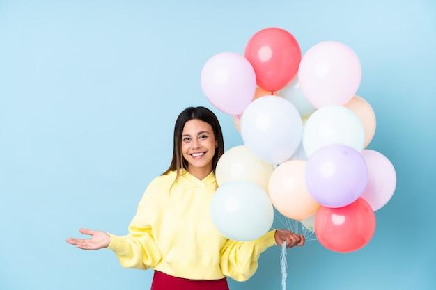 Donna che tiene i palloncini in una festa che tiene qualcosa sul palmo