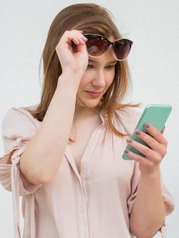 Donna che tiene i suoi occhiali e il telefono cellulare