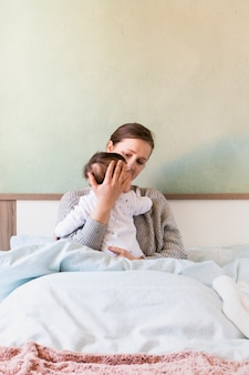 Donna che tiene il bambino in braccio a letto