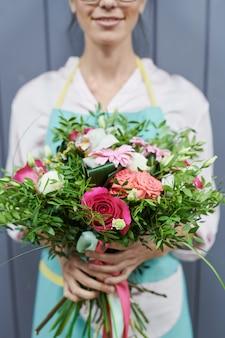 Donna che tiene il bello mazzo del fiore