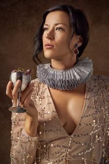 Donna che tiene il bicchiere di vino d'argento con uva viola