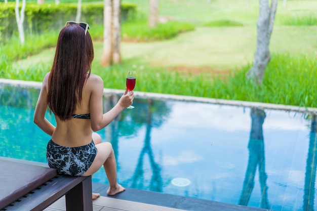 Donna che tiene il bicchiere di vino in piscina