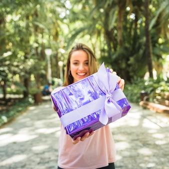 Donna che tiene il contenitore di regalo viola nel parco