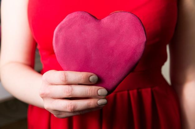 Donna che tiene il cuore rosso di amore a disposizione, primo piano del regalo di giorno di biglietti di s. valentino