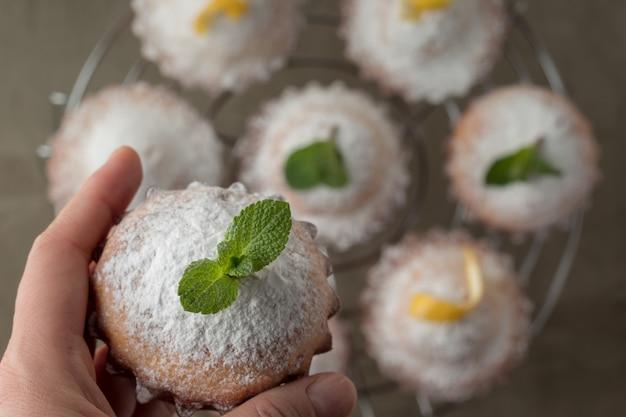 Donna che tiene il muffin saporito del limone con la polvere dello zucchero sopra la tavola, vista superiore con spazio per testo