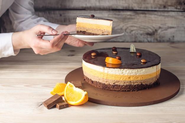 Donna che tiene il pezzo di torta al cioccolato all'arancia