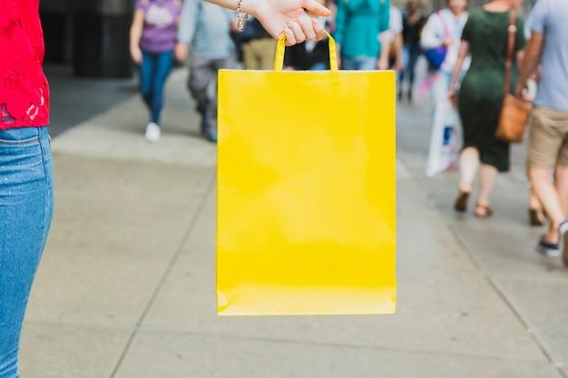Donna che tiene il sacchetto della spesa giallo