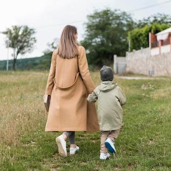 Donna che tiene il suo bambino per mano