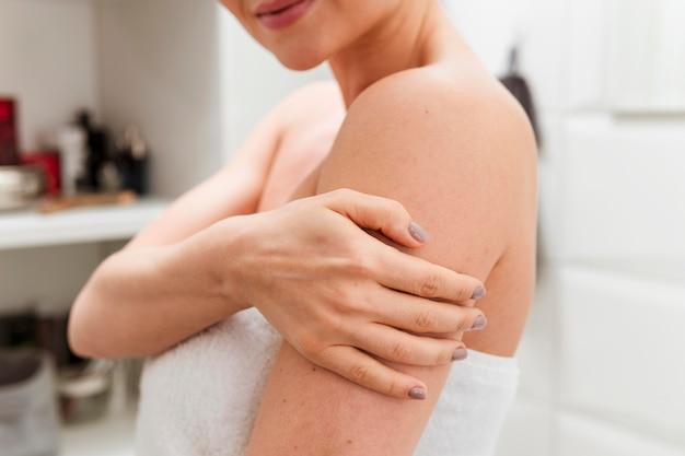 Donna che tiene il suo braccio nel bagno