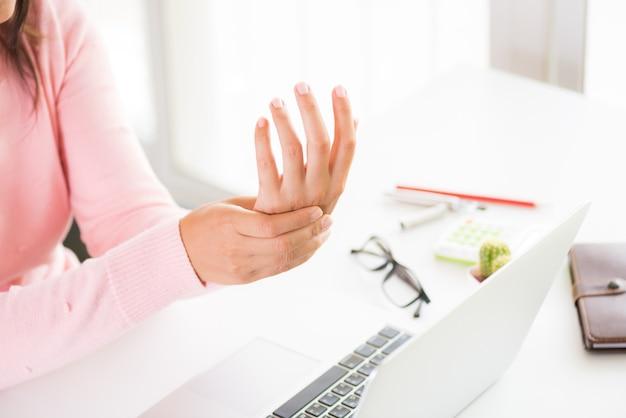 Donna che tiene il suo dolore al polso dall'uso del computer. sindrome da ufficio dolore alla mano