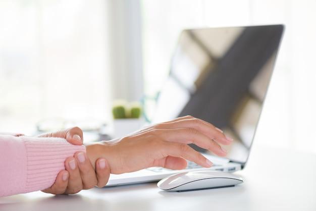 Donna che tiene il suo dolore al polso dall'uso del computer. sindrome da ufficio.