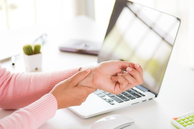 Donna che tiene il suo dolore al polso dall'uso del computer. sindrome da ufficio