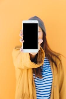 Donna che tiene il telefono cellulare con schermo vuoto in piedi di fronte a sfondo giallo