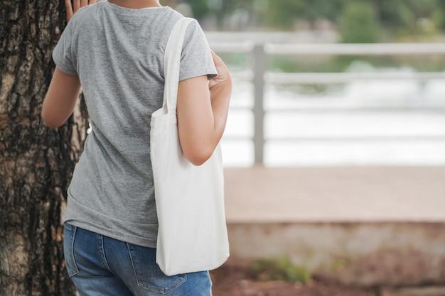 Donna che tiene in bianco tote bag vuota