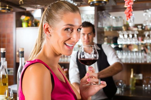 Donna che tiene in mano un bicchiere di vino al bar