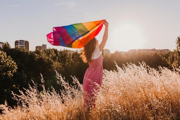 Donna che tiene la bandiera arcobaleno gay al tramonto. felicità, libertà e concetto di amore per le coppie dello stesso sesso. stile di vita all'aperto