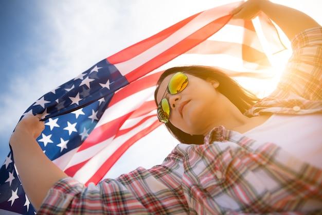 Donna che tiene la bandiera degli stati uniti d'america, concetto di festa dell'indipendenza degli stati uniti.
