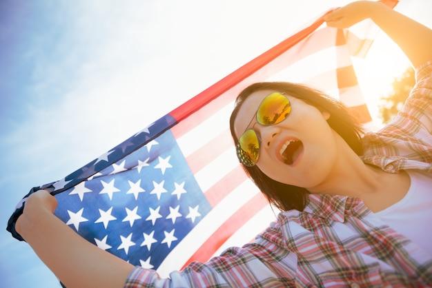 Donna che tiene la bandiera degli stati uniti d'america e in esecuzione sulla spiaggia.