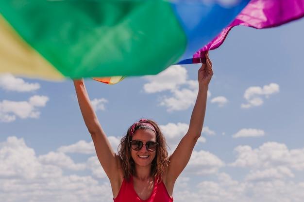 Donna che tiene la bandiera gay dell'arcobaleno sopra il cielo blu e nuvoloso all'aperto. felicità, libertà e concetto di amore per le coppie dello stesso sesso. lifestyle all'aperto