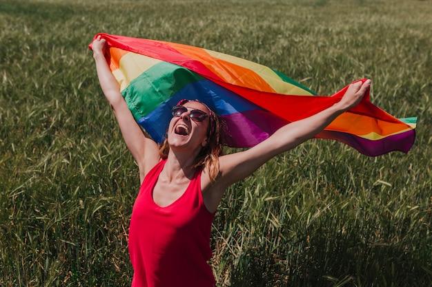Donna che tiene la bandiera gay dell'arcobaleno su un prato verde all'aperto. felicità, libertà e concetto di amore per le coppie dello stesso sesso. lifestyle all'aperto