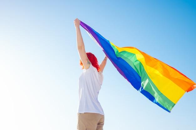 Donna che tiene la bandiera gay dell'arcobaleno sul fondo del cielo blu. felicità, libertà e concetto di amore per le coppie dello stesso sesso.