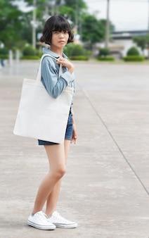 Donna che tiene la borsa del tessuto bianco al parco