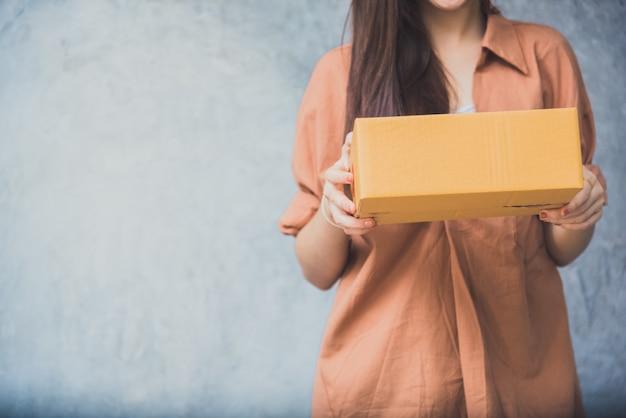 Donna che tiene la cassetta dei pacchi per la consegna al cliente con il servizio logistico