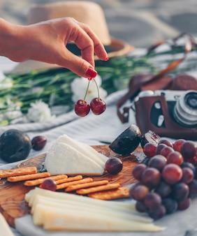 Donna che tiene la frutta con formaggio e frutta sul tagliere di legno e macchina fotografica, cappello e fiori in spiaggia.