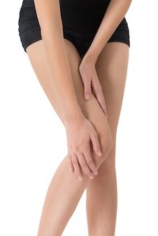 Donna che tiene la sua gamba con il massaggio del ginocchio e della coscia nell'area di dolore isolata su bianco