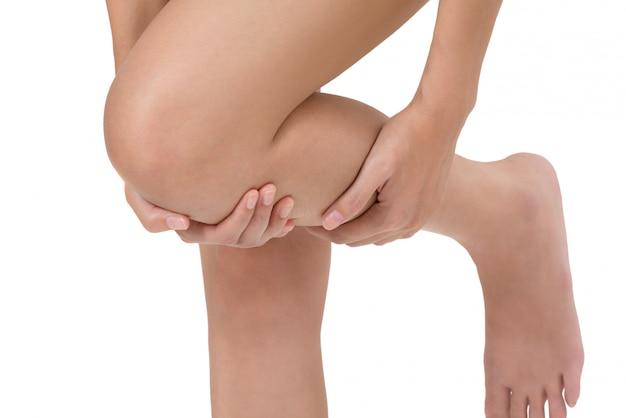 Donna che tiene la sua gamba con l'area di dolore shin di massaggio isolata su bianco