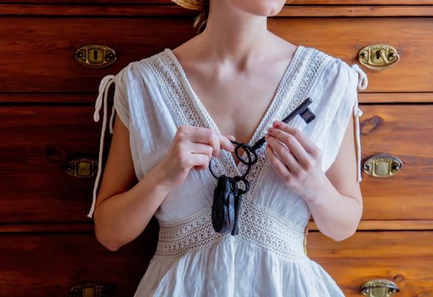 Donna che tiene la vecchia chiave aind lock na mani e stare vicino alla finestra con luce naturale