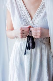 Donna che tiene la vecchia chiave e serratura in una mano e stare vicino alla finestra con luce naturale