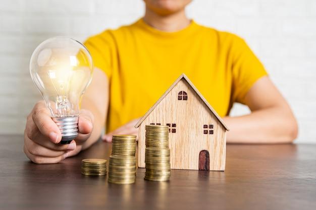 Donna che tiene lampadina con la moneta e la casa dei soldi sulla tavola, sul bene immobile e sull'offerta di scommessa e sul concetto di interesse basso
