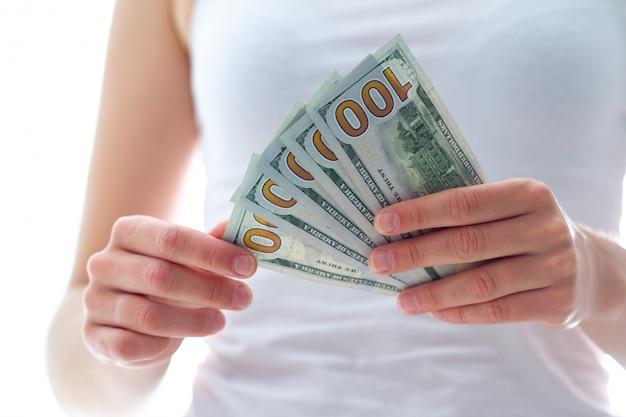 Donna che tiene le banconote in dollari americani. conteggio e distribuzione del denaro.