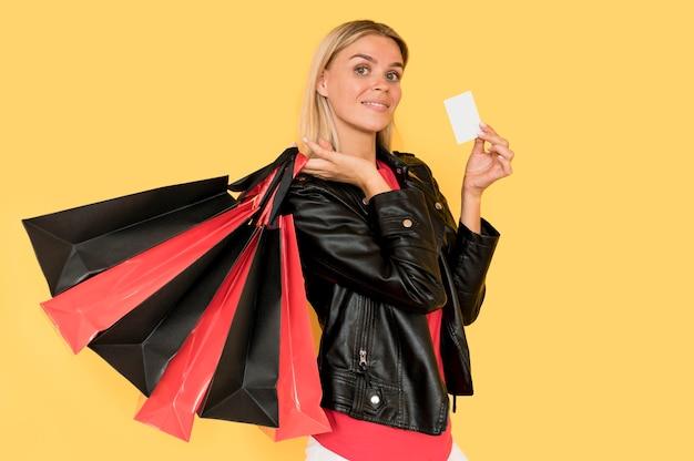 Donna che tiene le borse della spesa rosse e nere per le vendite del venerdì nero
