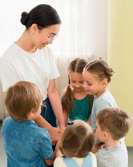 Donna che tiene le mani con i suoi studenti
