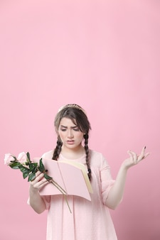 Donna che tiene le rose non capendo il libro che sta leggendo