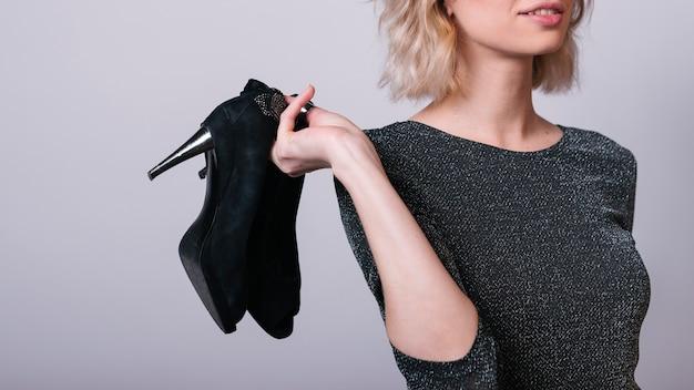 Donna che tiene le scarpe in mano