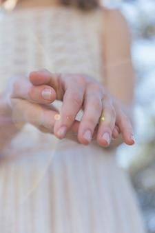 Donna che tiene le sue mani con luce solare