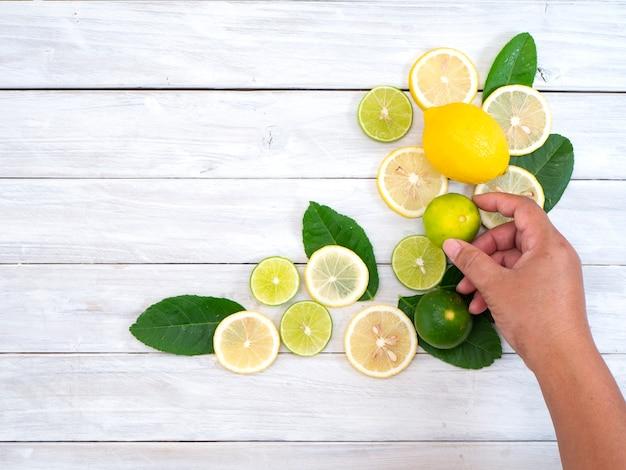 Donna che tiene limone fresco sulla tabella bianca