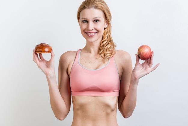 Donna che tiene mela e pasticceria