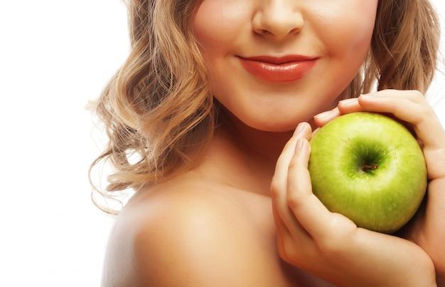 Donna che tiene mela verde.