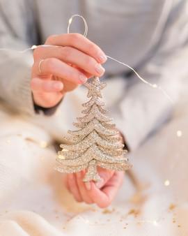 Donna che tiene piccolo albero di natale nelle mani
