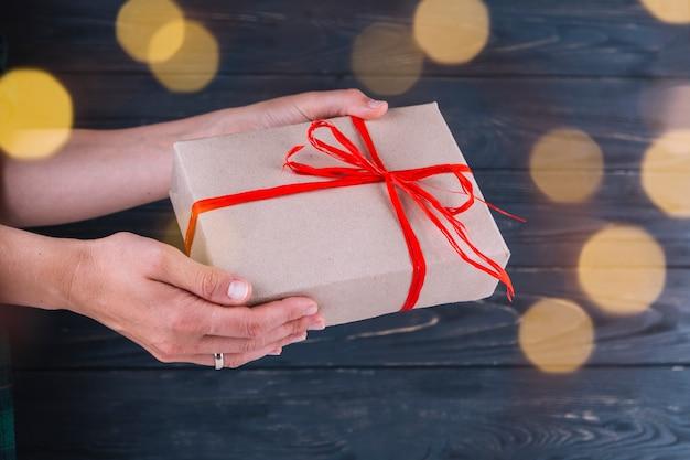 Donna che tiene piccolo contenitore di regalo in mano