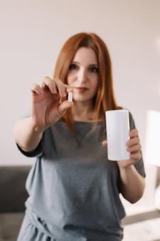 Donna che tiene pillola e bicchiere d'acqua bianchi.
