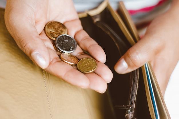 Donna che tiene portafoglio vuoto con alcune monete in sua mano - concetto di crisi economica - soldi di risparmio per contabilità finanziaria.
