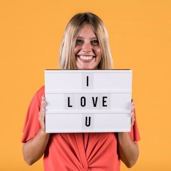 Donna che tiene scatola leggera con ti amo testo contro il semplice sfondo dello studio