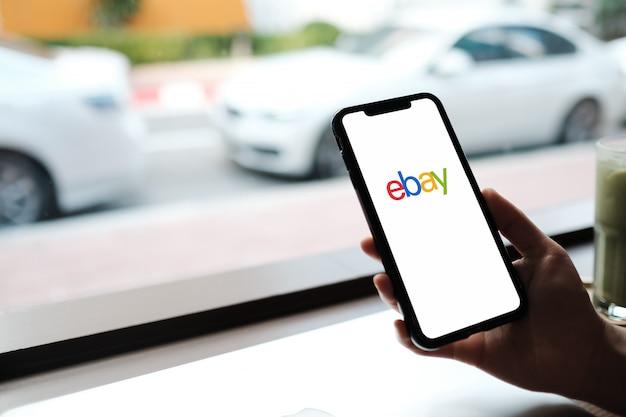 Donna che tiene smartphone con negozio online sullo schermo